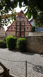 Baker baptism in front of the torture museum, torture instrument in front of a half-timbered house in Rothenburg ob der Tauber, Germany