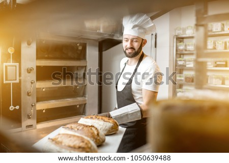 Baker carrying shovel with fresh baked breads standing near the professional oven in the bakery