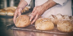 Baker checking freshly baked bread in the kitchen