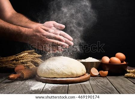 Baker cooking bread. Man slaps flour over the dough. Man Making bread