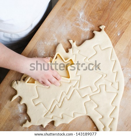 Baker cutting Christmas buscuits in the shape of Christmas Trees from a portion of rolled pastry, overhead view showing the cutouts