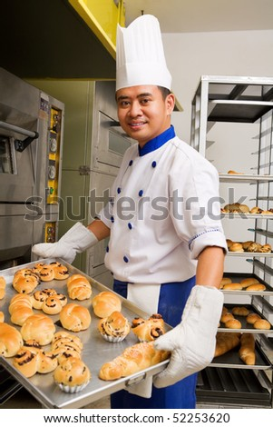 Baker holding the sweet bread fresh from the oven - stock photo