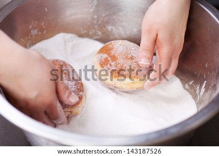 Baker is rolling doughnuts in container with sugar
