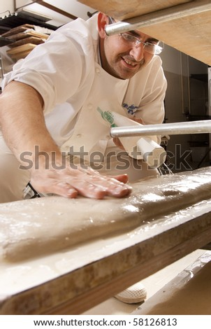 Baker makes the bread dough on the baking sheet in the oven to bake