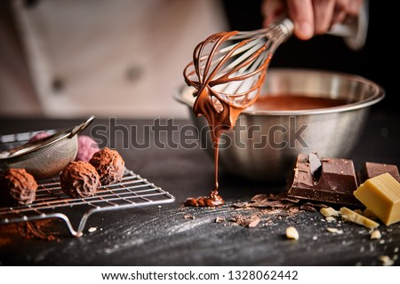 Baker or chocolatier preparing chocolate bonbons whisking the melted chocolate with a whisk dripping onto the counter below