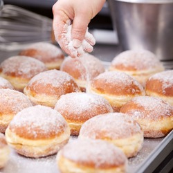 Baker pours sugar over pastry on a bakery tray