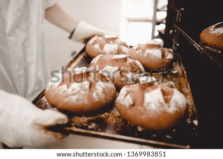 Baker pulls out of the oven a baking sheet the baking tray with newly-baked bread in the bakery #1369983851
