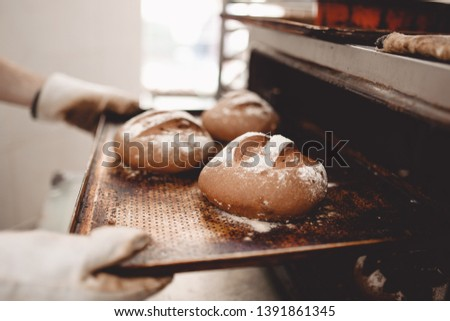 Baker pulls out of the oven a baking sheet the baking tray with newly-baked bread in the bakery #1391861345