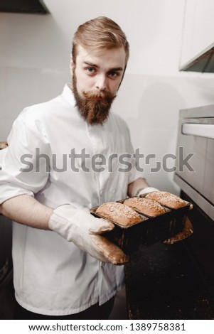 Baker pulls out of the oven a baking sheet the baking tray with newly-baked loafs of bread in the bakery #1389758381
