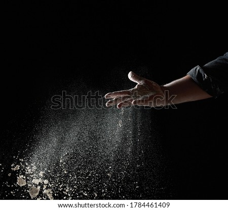 baker's hand throws a handful of white wheat flour on a black background, the particles fly in different directions Foto d'archivio ©