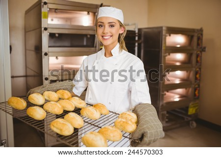 Baker smiling at camera holding rack of rolls in a commercial kitchen Stock photo ©