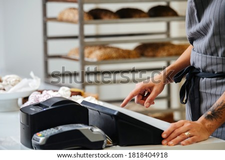Baker standing behing cash register calculating overal cost of the order. Side view. Cropped, no head. Сток-фото ©