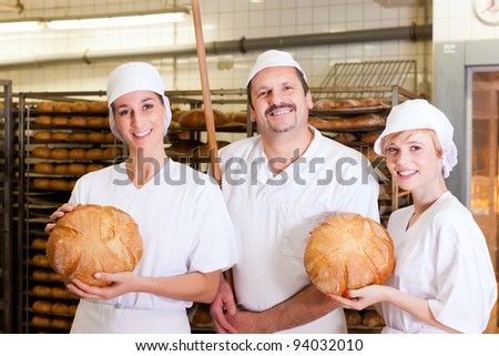 Baker standing with his team in bakery with freshly baked bread