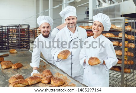 Bakers smiling holding fresh bread in their hands in a bakery ストックフォト ©