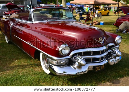 BAKERSFIELD, CA-APRIL 19, 2014: A very pretty maroon 1953 Cadillac convertible vies for attention among all the cars at the Cruisin\' For A Wish Car & Motorcycle Show.