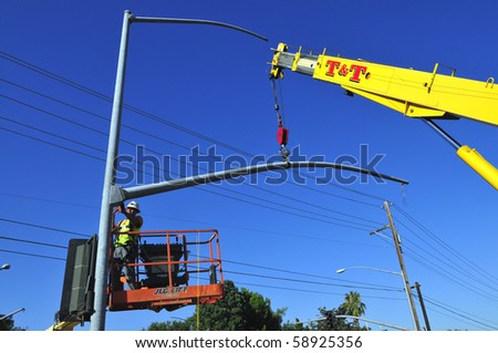 BAKERSFIELD, CA - AUG 12: Electricians completely replace traffic signals, poles and mast arms at a major intersection on August 12, 2010, at Bakersfield, California. Mast arm is bolted to the pole.