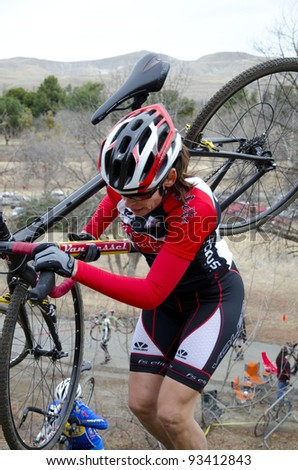BAKERSFIELD, CA - JAN 22: An unidentified woman struggles uphill with her bike on a dirt trail during the California State Cyclocross Championships on January 22, 2012, in Bakersfield, California.
