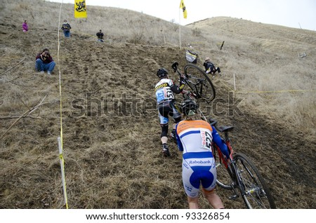 BAKERSFIELD, CA - JAN 22: Men riders dismount and struggle with their bikes uphill during the California State Cyclocross Championships on January 22, 2012, in Bakersfield, California.