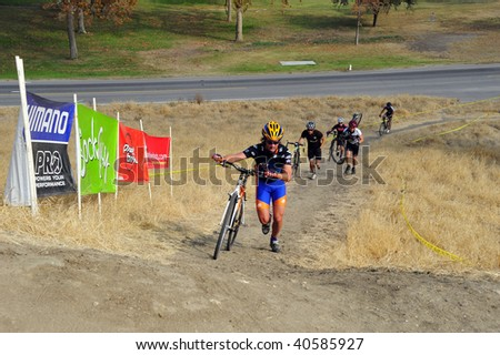 BAKERSFIELD, CA - NOV 7: Contestants dismount, carry their bikes uphill and remount during the Fifth Annual Hart Park Cyclocross on November 7, 2009, at Bakersfield, California.