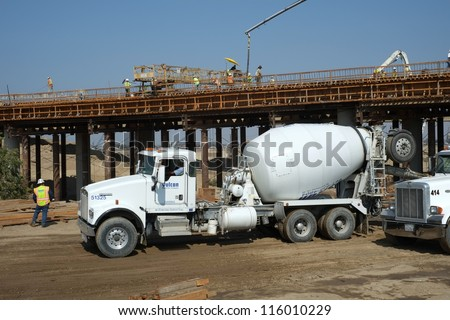 BAKERSFIELD, CA-OCT 16: Concrete pouring has begun on new bridge across the Kern River by pumping in flexible hoses fed by transit mix trucks on October 16, 2012, in Bakersfield, California.