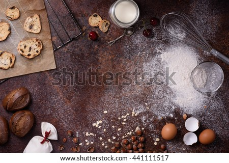 Bakery background, baking ingredients over rustic kitchen countertop. Baked cookies with hazelnuts, rye bread, milk and eggs. Top view, copy space.