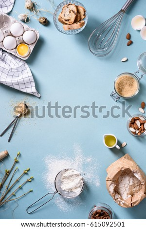Bakery background frame. Fresh cooking ingredients - egg, flour, sugar, butter, nuts over blue background. Spring cooking theme. Top view, copy space. #615092501