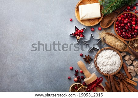 Bakery background with ingredients for cooking Christmas baking. Flour, brown sugar, butter, cranberry and spices on table top view.