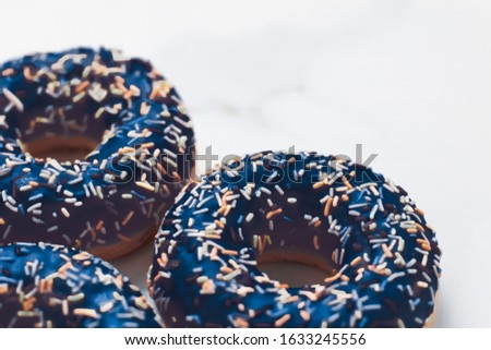 Bakery, branding and cafe concept - Frosted sprinkled donuts, sweet pastry dessert on marble table background, doughnuts as tasty snack, top view food brand flat lay for blog, menu or cookbook design