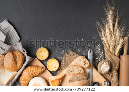bakery concept: bread, croissant, baguette, muffin and Egg Tart on black stone background