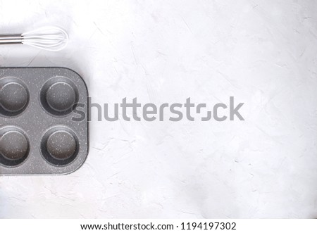 Bakery concept. Muffin tin Kitchen utensils Whisk. White background, Top view, Copy space, Flat lay. Minimal picture