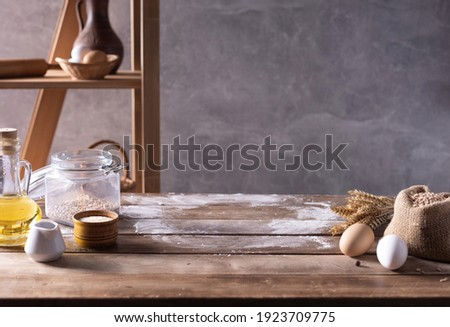 Bakery ingredients for homemade bread cooking or baking on table. Food set at wooden tabletop near wall background texture with copy space. Front view of bakery concept