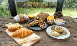 bakery on wood table butter croissant almond croissant spinach chesse waffle muffin cookie bread  whole wheat boule sourdough farmer boule fresh orange a cup of hot coffee green grass background