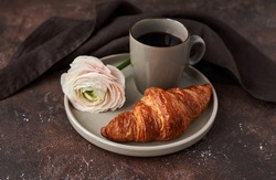 bakery product with cup of cofee and white flower on plate brown background