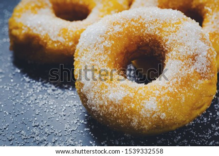 Bakery sweet donuts sprinkled with sugar powder on white plate on black table background Breakfast cake dessert food high calories
