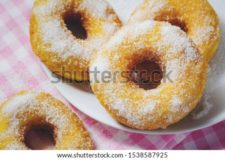 Bakery sweet donuts sprinkled with sugar powder on white plate on napery background Breakfast cake dessert food high calories