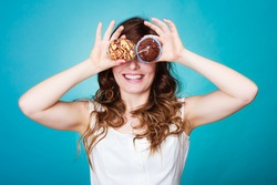 Bakery, sweet food and happiness concept. Closeup smiling woman having fun holding cakes in hands covering eyes with cupcakes blue background