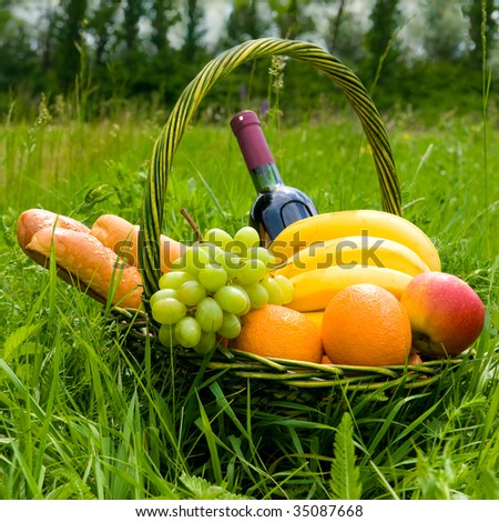 baking a fruit basket and a bottle of wine on the green grass