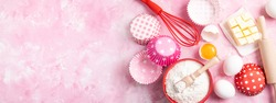 Baking background. Food ingredients for baking flour, eggs, sugar on pink background flat lay. Baking or cooking cakes or muffins. Long format with copy space. Top view