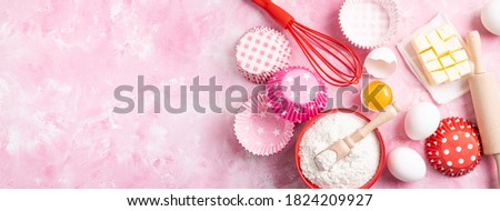 Baking background. Food ingredients for baking flour, eggs, sugar on pink background flat lay. Baking or cooking cakes or muffins. Long format with copy space. Top view Stock foto ©