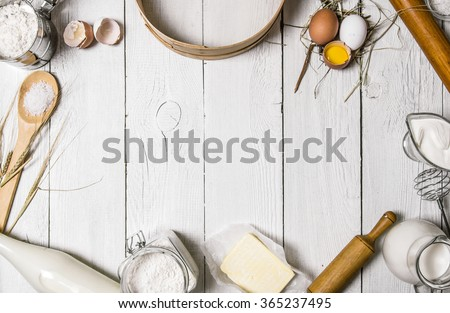 Baking background. Ingredients for the dough - Milk, eggs, flour, sour cream, butter, salt and different tools. On a white wooden background. Free space for text . Top view