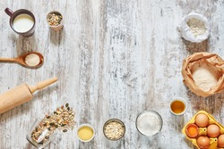 Baking background. Wholegrain flour, eggs in a carton tray, oat flakes, grains and seeds, milk, olive oil, rolling pin, wooden spoon over light rustic table. Space for text.