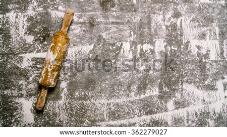 Baking background with a rolling pin with flour. On the stone table. Free space for text . Top view