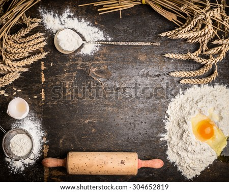 Baking background with bake tools, flour,egg and rolling pin on rustic wooden background, top view