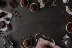 Baking background with chocolate muffins, measuring cups, chocolate, sugar, wrapping paperand nuts, on dark concrete background. Flat lay with copy space.