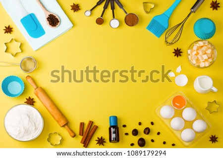 Baking background with eggs, flour, milk, spices cocoa, soda, anise, cinnamon, nutmeg, salt, coffee beans and kitchen tools rolling pin, wooden spoons, whisk, sieve, bake ware shape cookie cutter