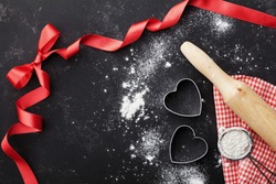 Baking background with flour, rolling pin and heart shape on kitchen black table from above for Valentines day cooking. Flat lay style.