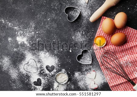 Baking background with flour, rolling pin, eggs, and heart shape on dark kitchen table top view for Valentines day cooking. Flat lay style #551581297