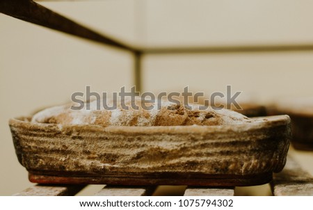 Baking bread  Dough in proofing basket on wooden table with
