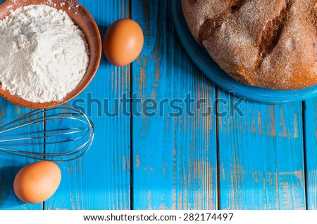 Baking cake in rural kitchen - dough recipe ingredients eggs, flour, butter, bread and whisk on vintage wood table from above. Rustic background with free text space.