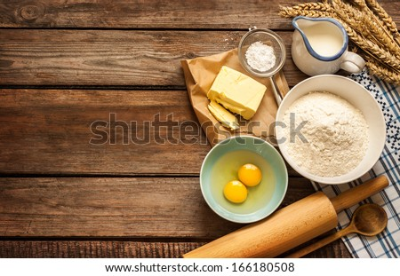 Baking cake in rural kitchen - dough recipe ingredients (eggs, flour, milk, butter, sugar) and rolling pin on vintage wood table from above. Rustic background with free text space.